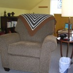 An alpaca blanket crocheted by my sister decorates a comfortable recliner.